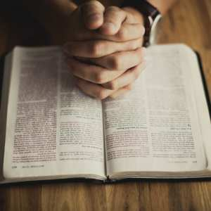 Hands folded over a bible